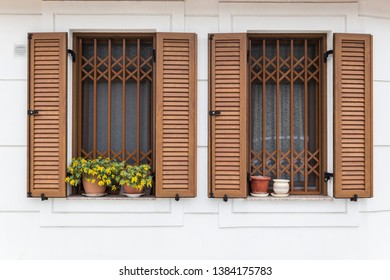 Windows with wooden louvers and flowering flower pots.