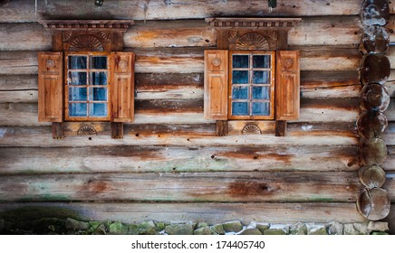 Windows of a wooden snow hut with white landscape reflected
