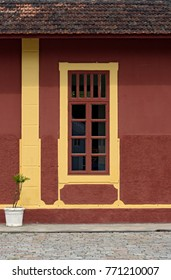 Windows with yellow frame on red wall, in old train station, in Brazil
