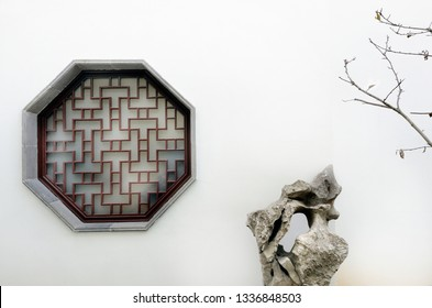 Window,stone and tree at the Garden of the Humble Administrator , Suzhou, China. This is an UNESCO World Heritage Site