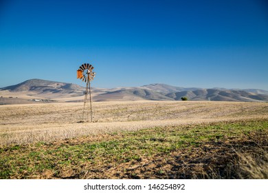 Windpump and hills A wind pump in the middle of dry fields with hills in the background