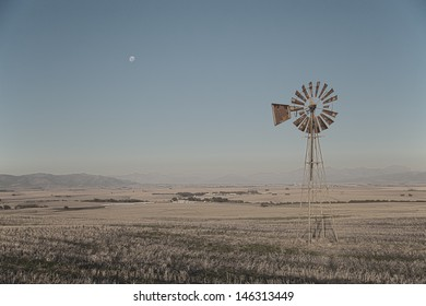 Windpump and moon A country side landscape with a wind pump in the middle of dry fields and the moon in the sky