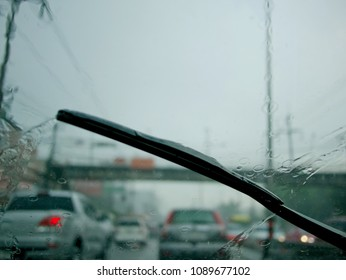 Windscreen wiper arm and blade removing rain from the windscreen