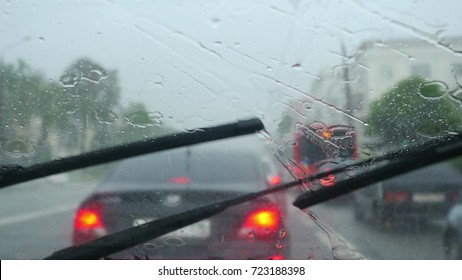 Windscreen wipers cleaning windshield glass on deep rainy day