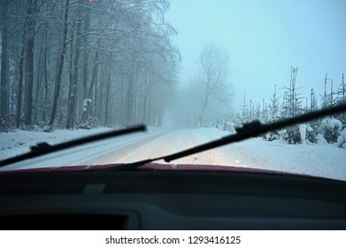 Windscreen wipers. Driving the car in the winter. View from the interior of a car on a snowy road by the eyes of the driver. Concept for driving safety in the winter.
