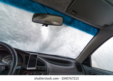 windshield of car in soap. car wash concept. view from inside