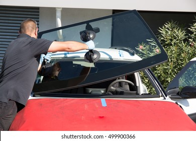 Windshield replacement, man is changing windscreen on a car