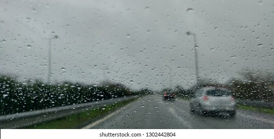 Windshield view of road traffic in bad weather.