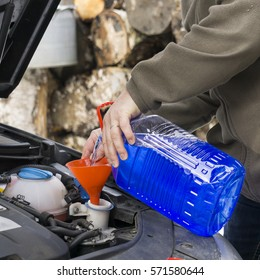 Windshield washer fluid being poured into a vehicle's storage tank