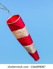 A windsock  in an airport against blue sky. A windsock is a conical textile tube, used as a basic guide to wind direction and speed.