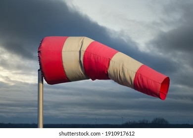 Windsock in Dutch rural landscape with heavy wind and stormy sky
