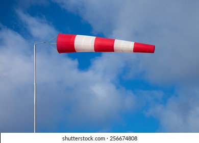 windsock indicating strong wind on blue sky with light clouds background