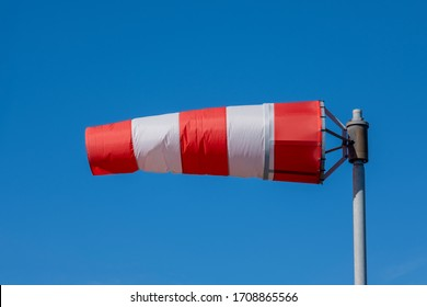 Windsock indicator of wind on runway airport. Wind cone indicating wind direction and force. Horizontally flying windsock (wind vane) with blue sky in the background
