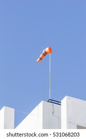 windsock on clear blue sky background in windy weather