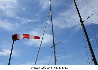 Windsock and yacht masts against blue sky with white clouds