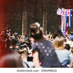 WINDSOR, BERKSHIRE, UNITED KINGDOM - MAY 19, 2018: Raised cameras and phones as carriage with newlyweds approach at royal wedding marriage celebration of Prince Harry and Meghan Markle - vintage