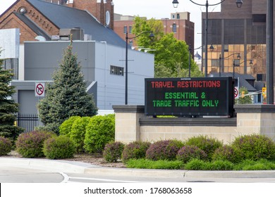 """Windsor, Canada - May 21, 2020: """"Travel Restrictions - Essential & Trade Traffic Only"""" sign at the entrance to the Detroit-Windsor, US-Canada Border crossing during the ongoing COVID-19 pandemic"""