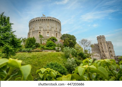 Windsor Castle with a blue sky background. The picture focuses on the Round Tower surrounded by the Moat garden. Windsor Castle is a royal residence at Windsor in the English county of Berkshire.