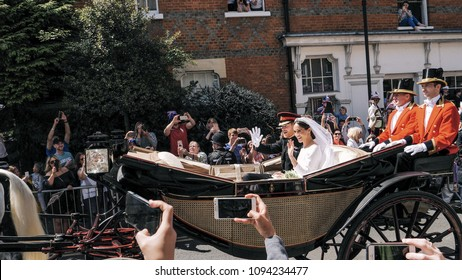 WINDSOR, ENGLAND - MAY 19 2018: Prince Harry, Duke of Sussex and Meghan Markle, Duchess of Sussex leave Windsor Castle in Ascot Landau carriage during a procession after getting married at St Georges