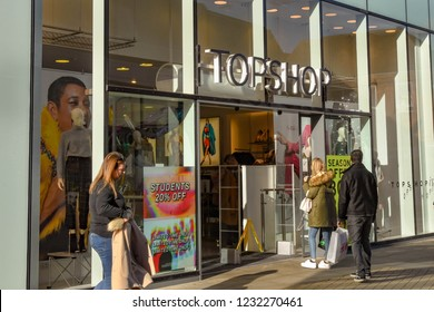 WINDSOR, ENGLAND - NOVEMBER 2018: Sign above the entrance to a branch of clothing chain Topshop, part of the Sir Phillip Green empire, in Windsor town centre. A customer is entering the store.
