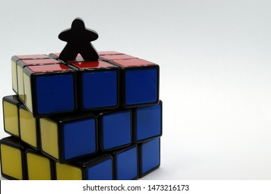Windsor, ON - August 2019: Meeple on top of a Rubik's cube. Reaching goal, climbing social ladder, getting on top, winning, problem solving, hard work concept.