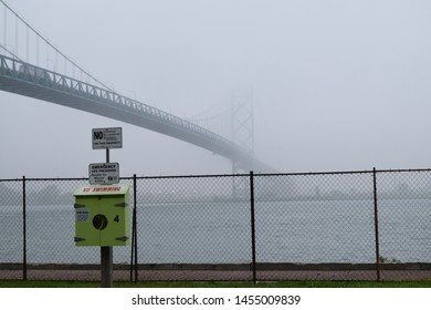 Windsor, ON - June 2019: Windsor waterfront signs with Ambassador Bridge in foggy background. River walk on a rainy day