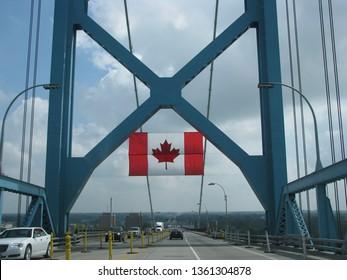 Windsor, Ont./Canada-Aug. 23, 2015: The maple leaf flag greets Canada-bound traffic on the Ambassador Bridge linking Detroit to Windsor.