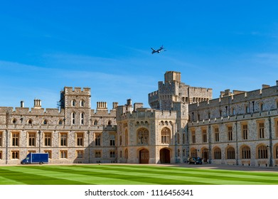 Windsor, UK - April 2018: Buildings at The Quadrangle of Windsor Castle, a royal residence at Windsor in county of Berkshire, England, UK, with an airplane flying over