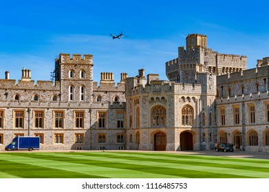 Windsor, UK - April 2018: Group of buildings at The Quadrangle of Windsor Castle, a royal residence at Windsor in county of Berkshire, England, UK, with an airplane flying over
