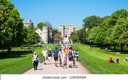 Windsor, UK - May 5, 2018:  medieval Windsor Castle, built 1066 by William the Conqueror. Official residence of Queen. People walking in the Park. Berkshire, England UK.