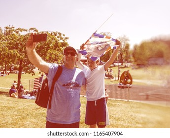 WINDSOR, UNITED KINGDOM - MAY 19, 2018: Father and son taking selfie with Prince Harry and Meghan Markel flag in Windsor after royal wedding - vintage effect