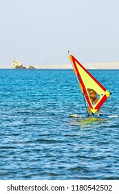 Windsurfer, blue sea and yellow sail. Windsurfing. Surfer exercising in calm sea or ocean