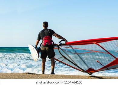 Windsurfer with board in the sea on Crete on sunset. Windsurfing in Heraklion. Greece