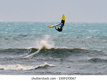 Windsurfer Catches a Wave and Takes to the Air Unrecognizable person in a wet suit on windsurf board as it has just gone over the peak of a wave and flipped up in midair. Sunny day with clear blue sky