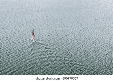 Windsurfer isolated on the cold blue lake water background