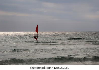 Windsurfer man silhouette on the backlight sea. Windsurfing man on the sea in the dusk.