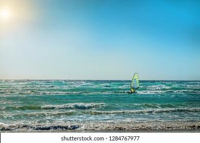 Windsurfer on the waves. Ocean coastline on the island. Sport, surf, windsurf, leasure, holidays concept.