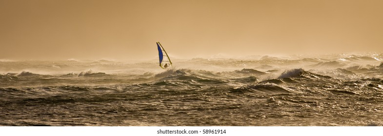 A windsurfer rides along the beautiful Maui's shores  a few minutes before sunset.