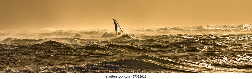 A windsurfer is riding along the beautiful Maui's shores while the sun is slowly setting on a perfect day