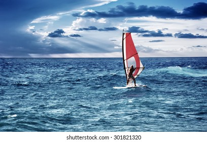 Windsurfer in the sea, man on windsurf conquering the waves, enjoying extreme sport, active lifestyle, happy summer vacation