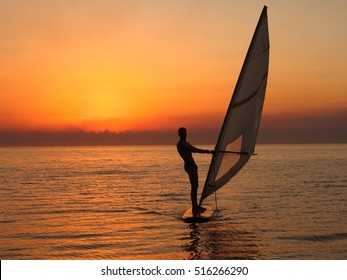 windsurfer silhouette against a sunset background - natural sky
