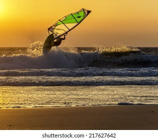 Windsurfer speeding fast against the sunset