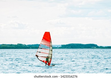 Windsurfer stands on the board and tries to catch a gust of wind