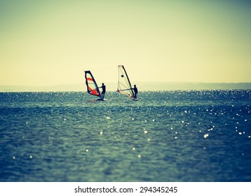 Windsurfers swimming in sea. Summertime photo with windsurfers swimming on water surface