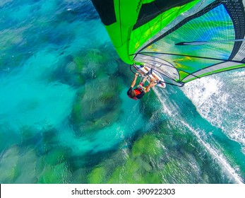 WIndsurfing flight over coral reef and cristal clear water