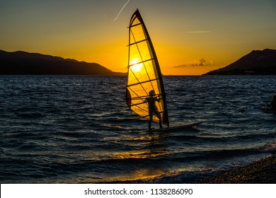 Windsurfing at sunset. Perfect activity for summer.