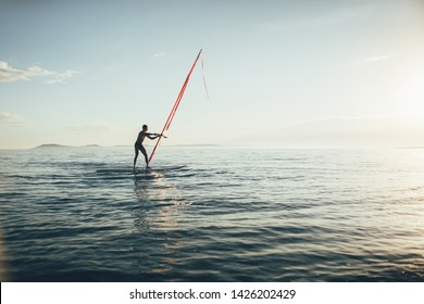 Windsurfing. Surfer catching the wind on the wind surfer board
