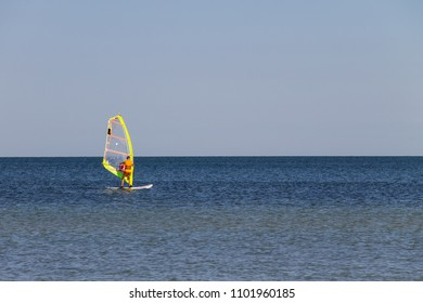 Windsurfing. Surfer exercising in calm sea or ocean. Recreational water sports during idyllic summer vacation