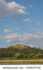 Windturbine as seen from the autobahn surrounded with white clouds. The small hill makes it look like an lonley windturbine.