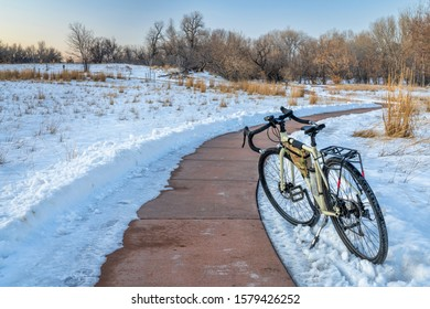 windy bike trail with a bicycle on kickstand in winter sunset scenery - Poudre River Trail in Fort Collins, Colorado, recreation and commuting concept